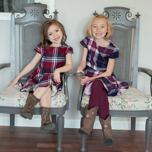 Girls in chair wearing plaid dresses.